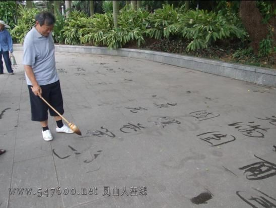 an old man practice penmanship on the ground